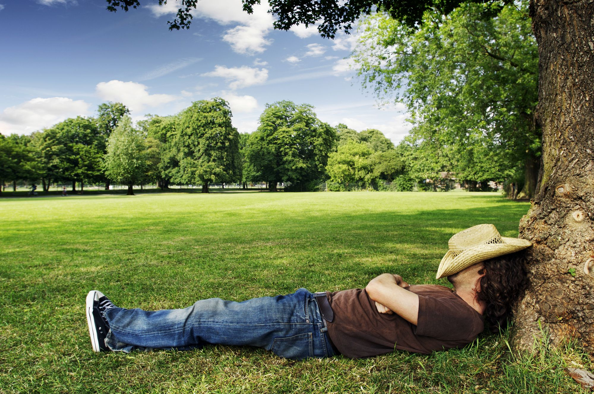man with hat over his head sleeping under a tree