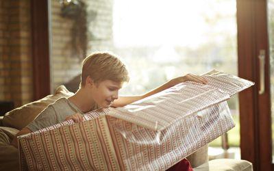 preteen boy opening a big present