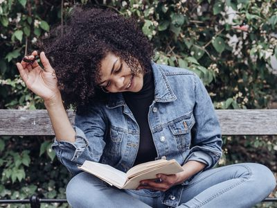 Woman smiling and reading a self-help book.