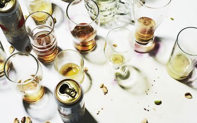 collection of empty glasses and beer cans on table