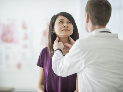 A doctor checking a woman for a thyroid problem.