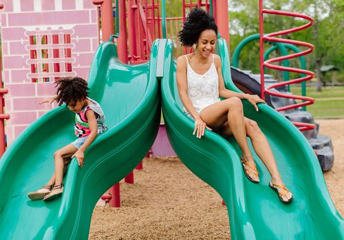 Mother and daughter playing on slide at playground