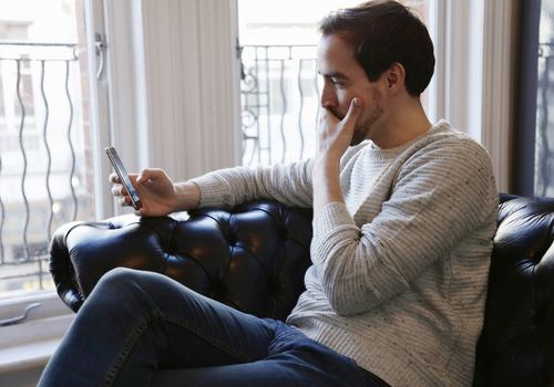 Man looking at his phone with a worried expression.