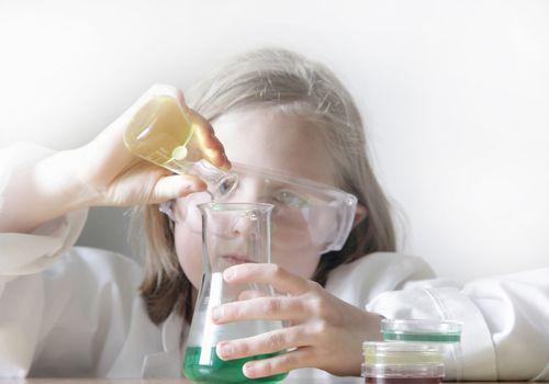 Girl pouring liquid into beakers