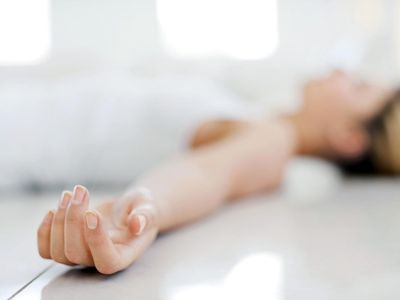 Young woman relaxing on floor, focus on hand