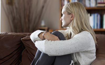 Anxious woman sitting in sofa daydreaming