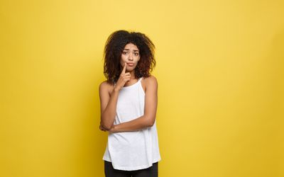 Portrait Of Thoughtful Young Woman Standing Against Yellow Background