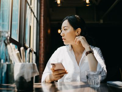 woman sitting in cafe looking out window