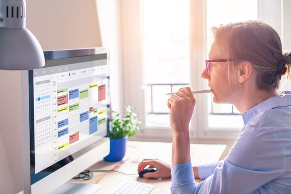 woman blocking out time on computer
