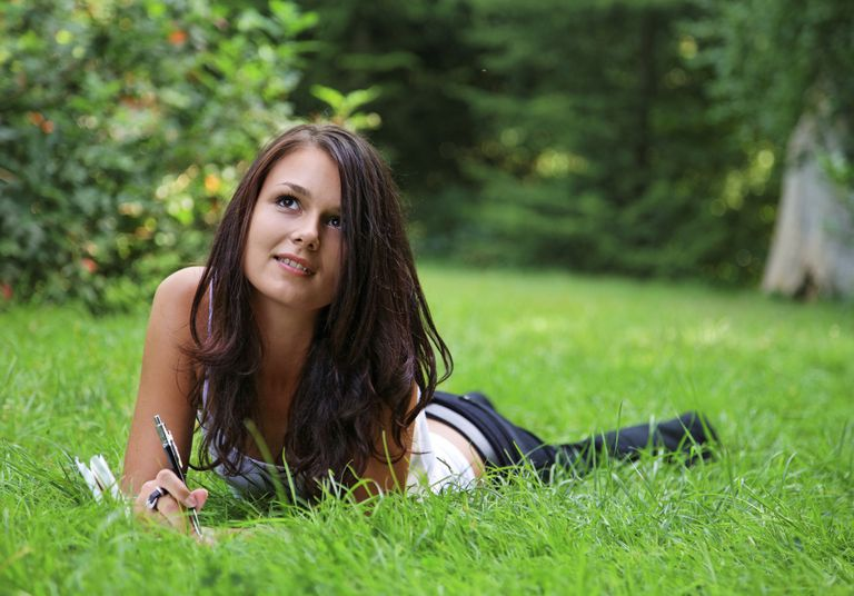 young woman journaling in the grass