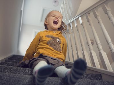 Young child sitting on staircase with mouth open