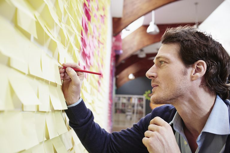 Businessman writing on sticky note at wall