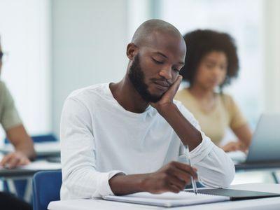 Black man sitting at a desk writing and thinking