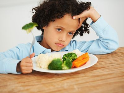 young boy not eating his broccoli