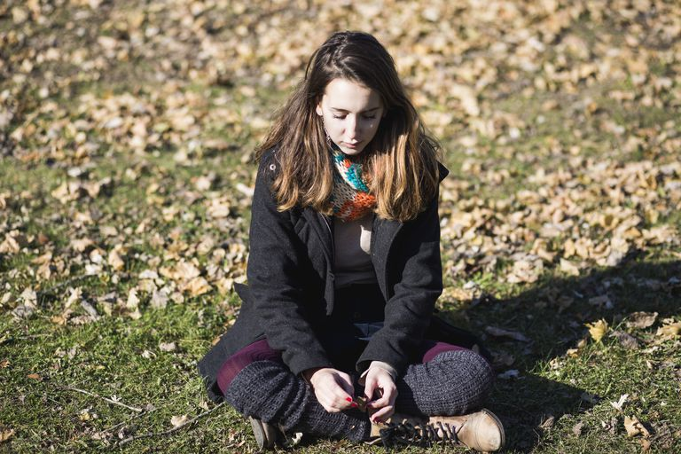 Portrait of a girl sitting on the ground with a lot of leaves