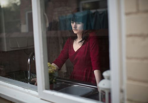 Sad woman standing in kitchen