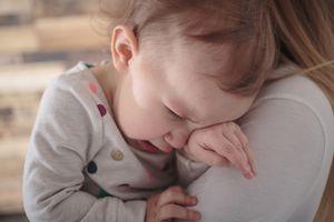 Toddler girl crying on mothers shoulder