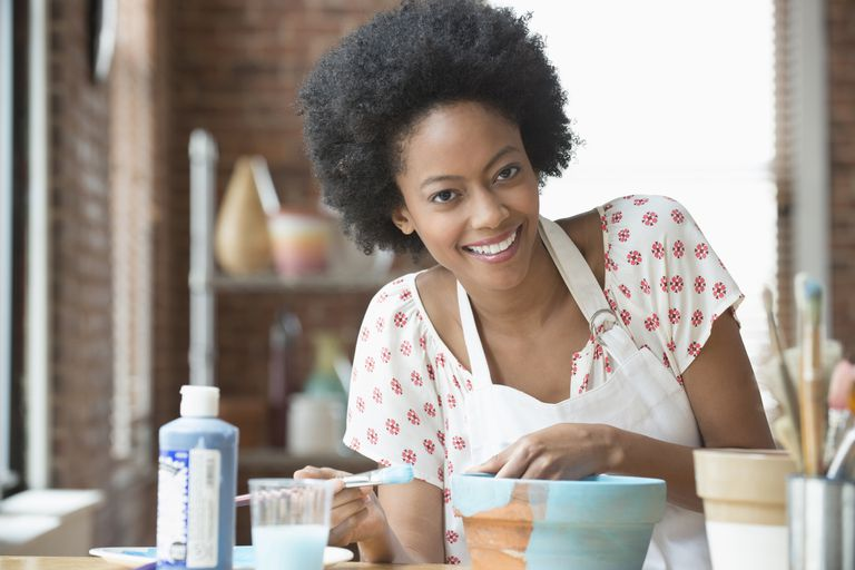 woman smiling and painting pottery