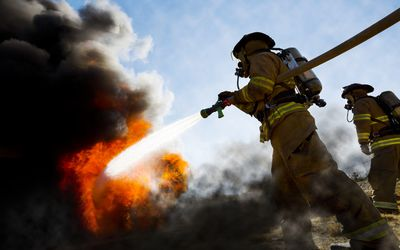 Firefighters using hose to fight fire