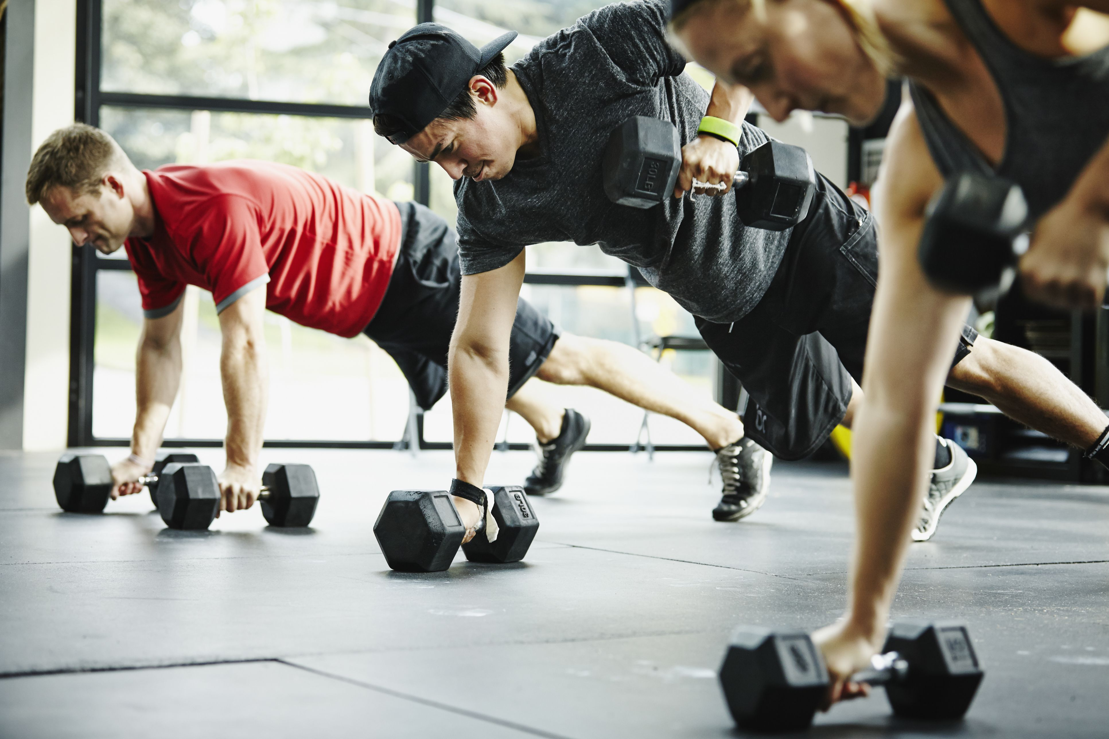 Row of people in plank position doing rows with dumbells