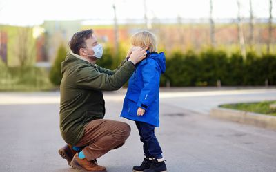 Dad putting a mask on his son