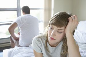Couple sitting on opposite sides of the bed, close-up of young woman looking distressed