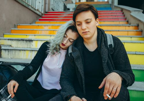 A sad couple of teens embrace, with cigarettes in hand, on colorful stairs in Istanbul.