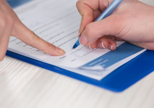 Woman's hand shown signing a contract