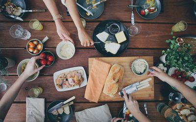 overhead view of people's hands reaching for food at table