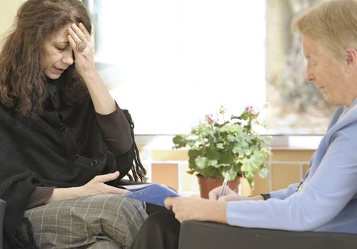 Distressed woman holding her hand to her head in a counselling session with a male therapist