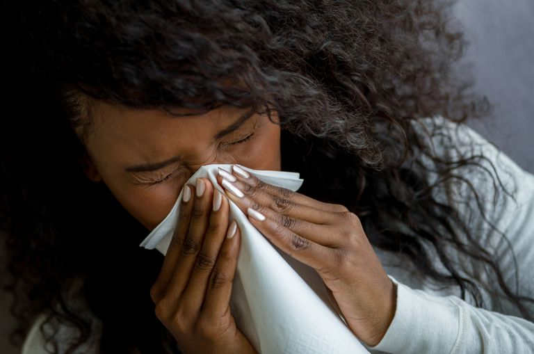 Black woman with the flu blowing her nose
