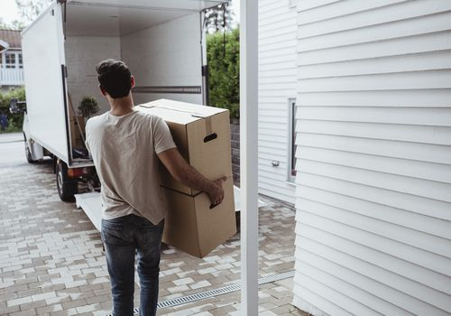 Rear view of man carrying cardboard boxes towards van