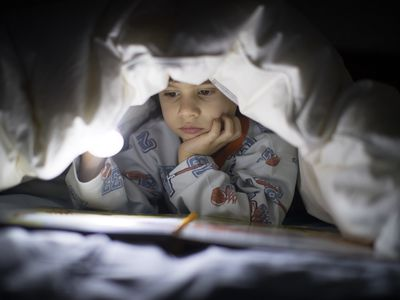 5 year old boy reading a book in the dark