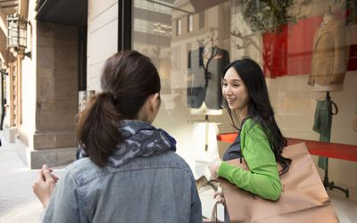 Two smiling female friends window shopping