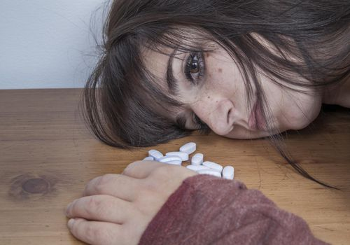 Woman with her head resting on a table next to a pile of pills