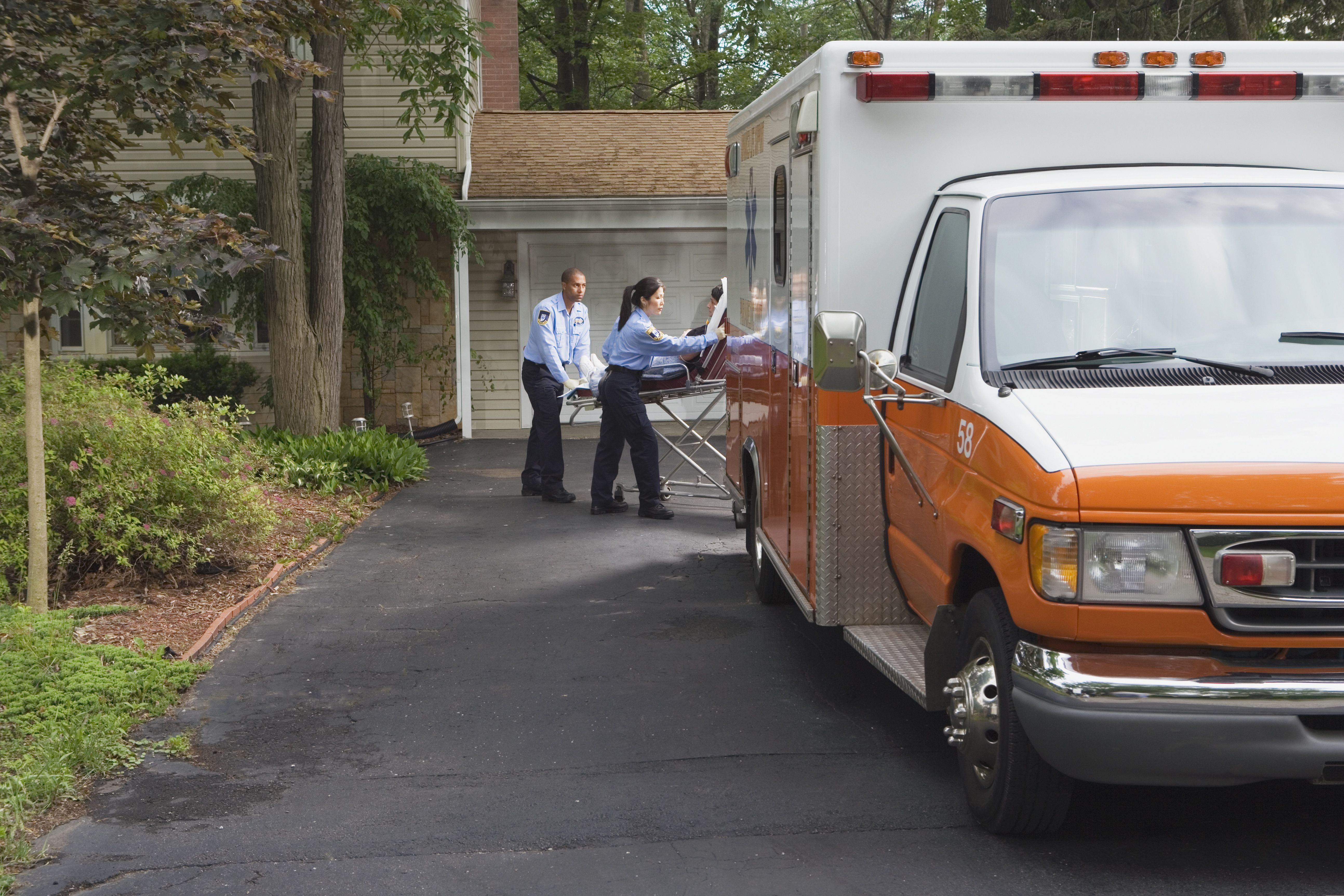 Paramedics putting person in ambulance in driveway