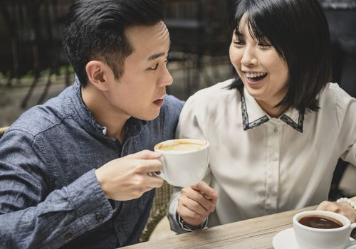Chinese woman laughing at boyfriend with coffee froth on lip