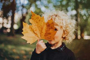 Child holding a leaf in front of their face