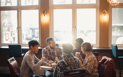 Small group of people with a mixed age range sitting around a table in a cafe