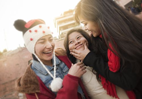 Three female friends laughing and smiling outodoors