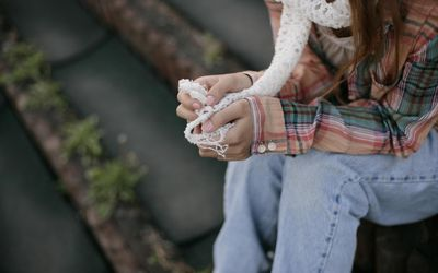 close-up of young woman's hands holding white scarf