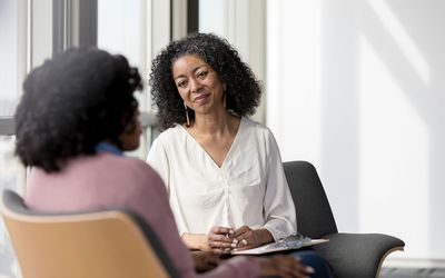 Mature counselor listens compassionately to female client