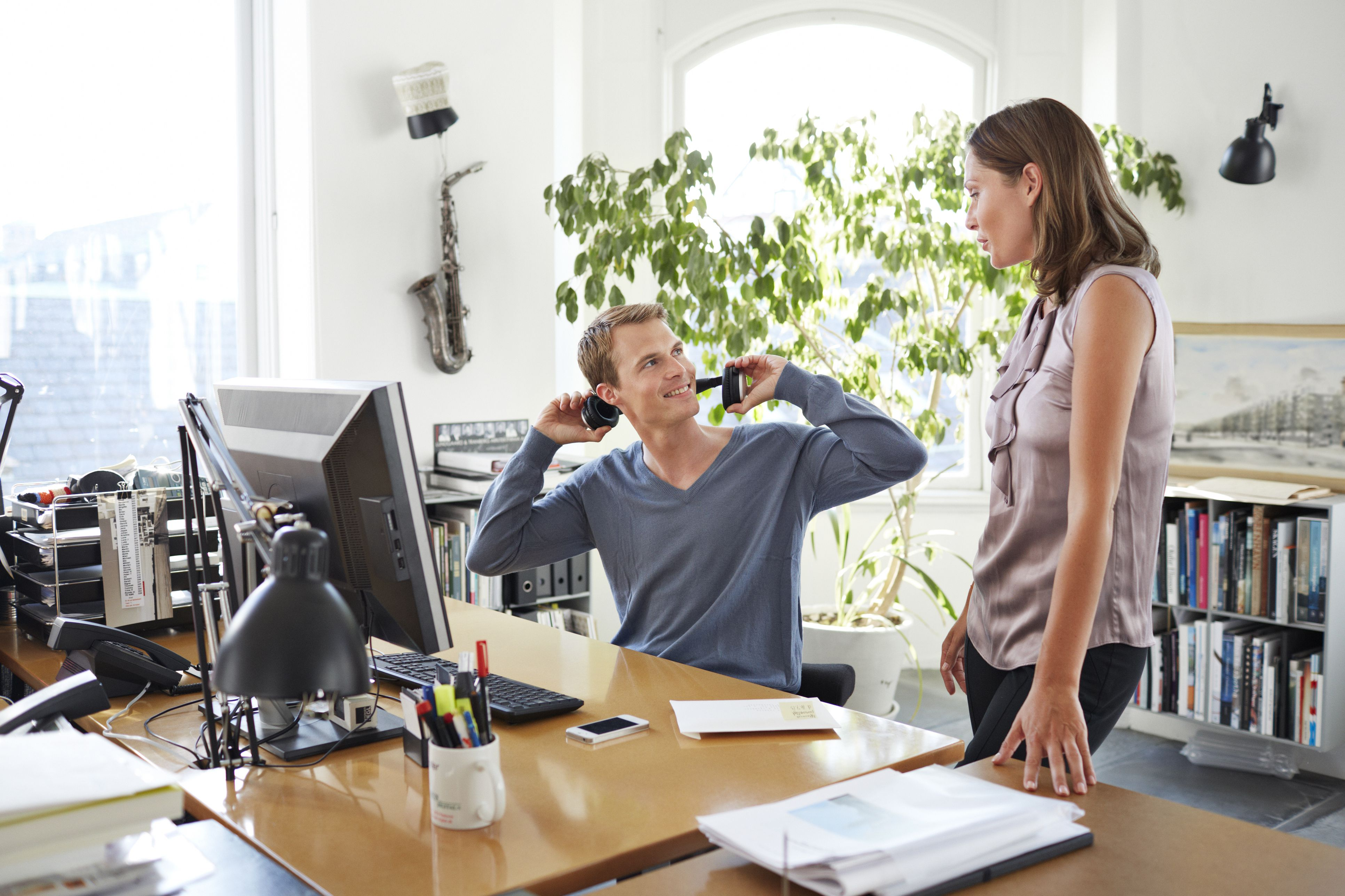 Woman talking to co-worker who is taking off his headphones