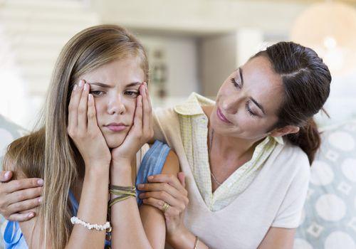 Mother trying to comfort her upset teen daughter