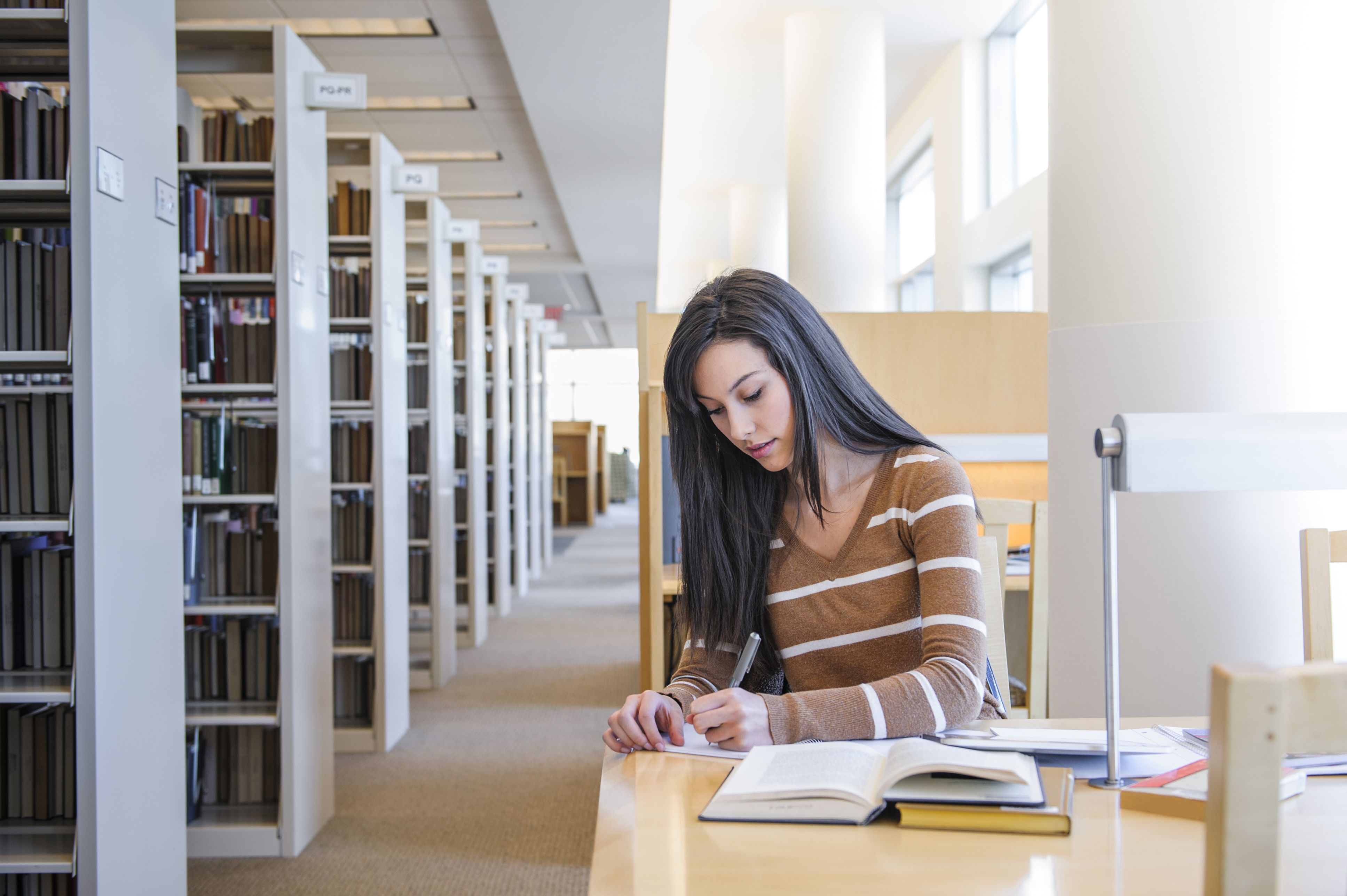 Young woman researching paper in library