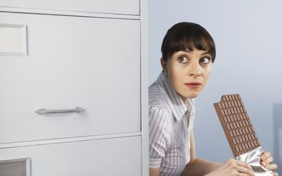 Office worker hiding and eating a large block of chocolate
