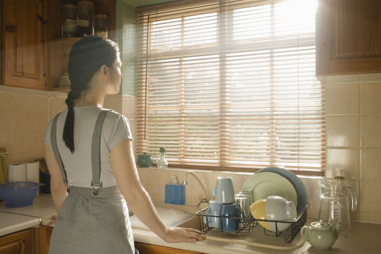 Woman doing dishes looking out window.