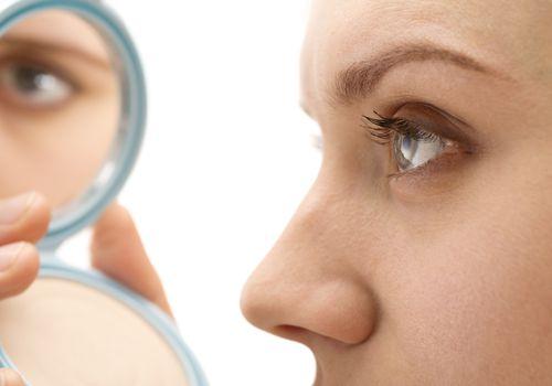 Woman applying makeup eye reflection