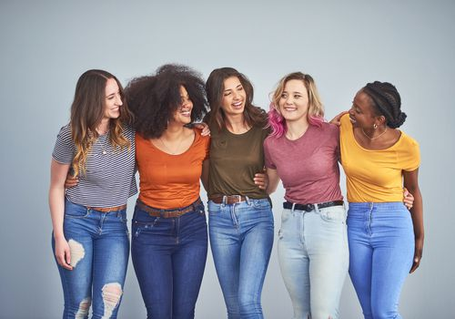 Studio shot of a group of attractive young women embracing against a gray background