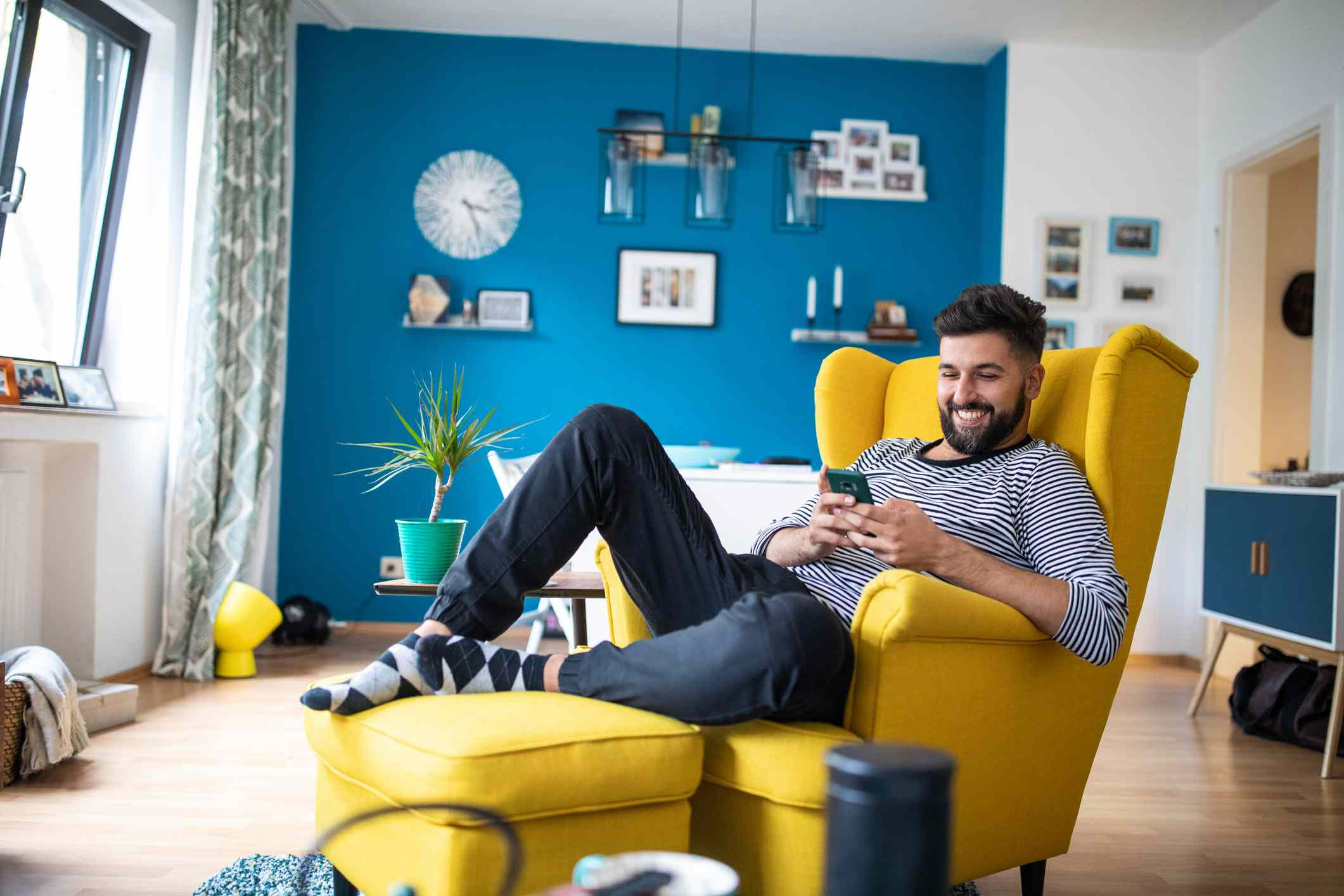 Young man laughing while holding his phone and sitting in his apartment
